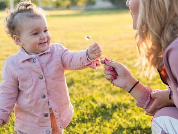 Enfant En Vêtements Roses Tenant Une Fleur Photo gratuit