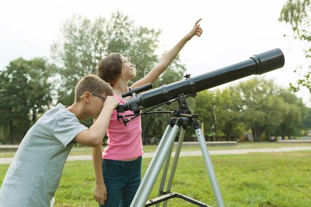 Enfants adolescents avec télescope regardent le ciel dans la nature Photo Premium