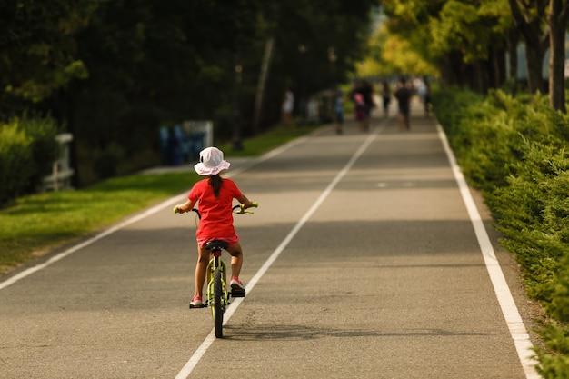 Enfants apprenant à conduire un vélo dans une allée à l'extérieur. Photo Premium