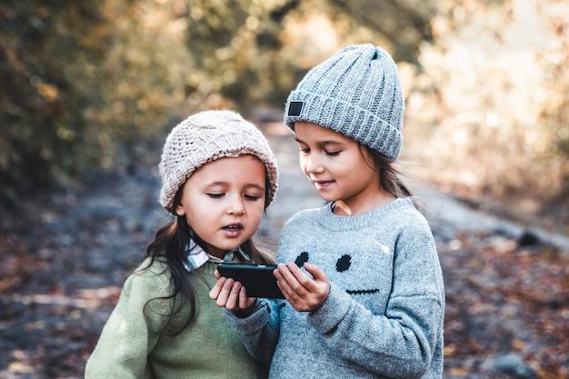 Les Enfants En Arrière-plan De La Nature Jouent Avec Un Smartphone. Regardez La Vidéo Et Amusez-vous. Relation Amicale Photo Premium
