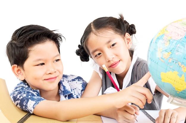 Enfants asiatiques étudient le globe sur fond blanc Photo gratuit