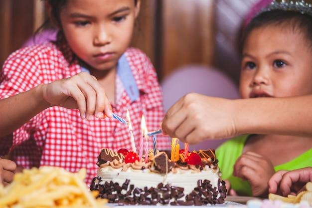 Enfants Asiatiques Filles Et Garçons Allumer La Bougie Sur Le Gâteau D'anniversaire Ensemble Dans La Fête D'anniversaire Photo Premium
