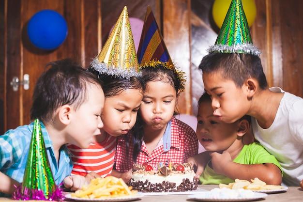 Enfants Asiatiques Filles Et Garçons Célébrant L'anniversaire Et Soufflant Des Bougies Sur Le Gâteau D'anniversaire Dans La Fête Ensemble Photo Premium