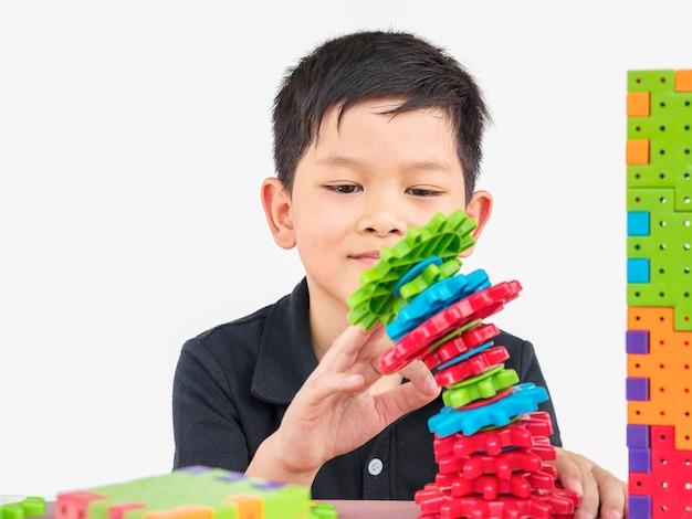 Les enfants asiatiques jouent au jeu créatif de bloc en plastique de puzzle Photo gratuit