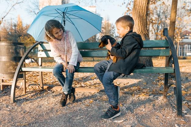 Enfants assis sur un banc avec un chien de teckel Photo Premium