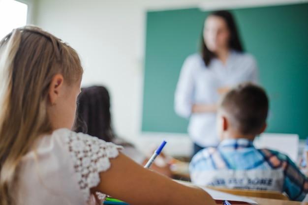 Enfants assis dans la salle de classe sur le cours Photo gratuit