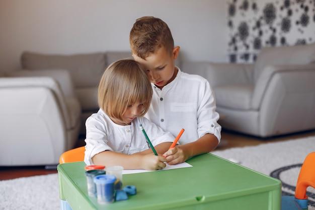 Enfants Assis à La Table Verte Et Dessinant Photo gratuit