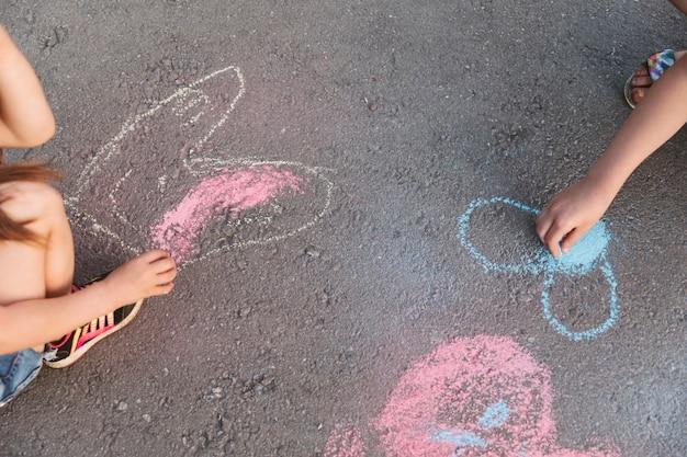 Enfants au grand angle faisant des dessins à la craie Photo gratuit