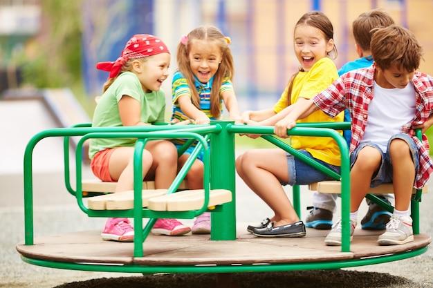 Les enfants ayant l'amusement carrousel Photo gratuit