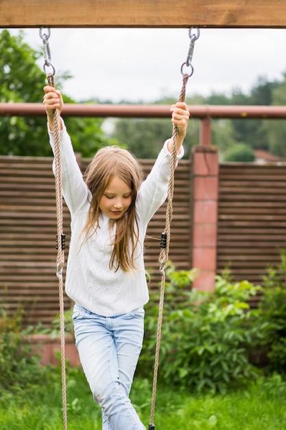 Les Enfants Sur La Balançoire. Fille Se Balancer Sur Une Balançoire Dans La Cour. Plaisirs De L'été. Photo gratuit