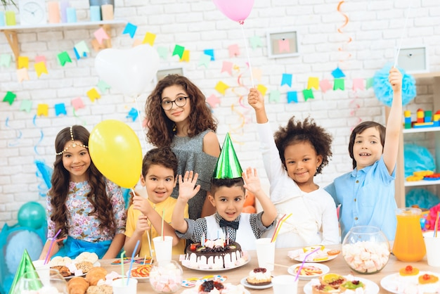 Les enfants avec des ballons de couleur sont assis derrière la table de fête. Photo Premium
