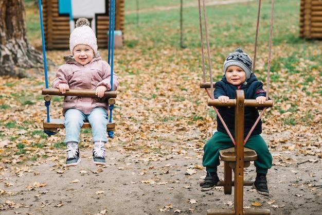 Enfants en bas âge se balançant dans le parc Photo gratuit