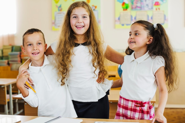 les enfants en blouse blanche posant des sourires. Black Bedroom Furniture Sets. Home Design Ideas