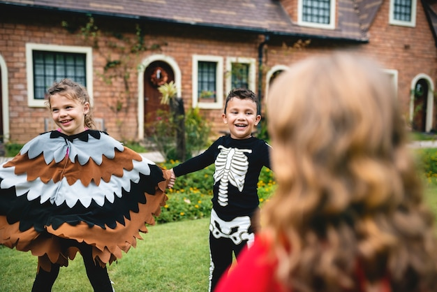 Enfants en costumes d'halloween se tenant la main dans un parc Photo Premium