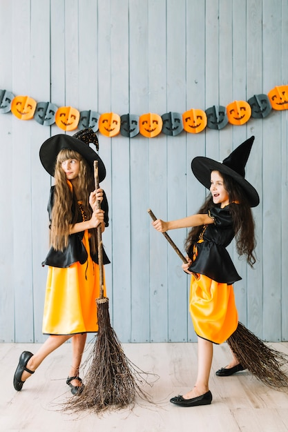 Enfants En Costumes De Sorcière Tenant Des Balais Photo gratuit