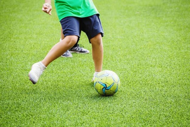 Enfants courir et donner un coup de pied au ballon de football Photo Premium