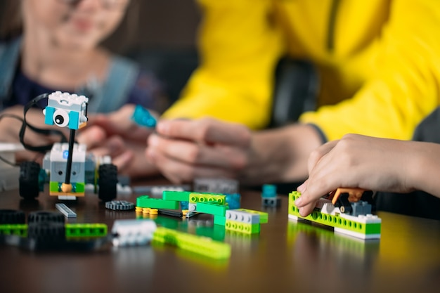 Enfants créant des robots avec un enseignant. développement précoce, bricolage, innovation, technologie moderne. Photo Premium