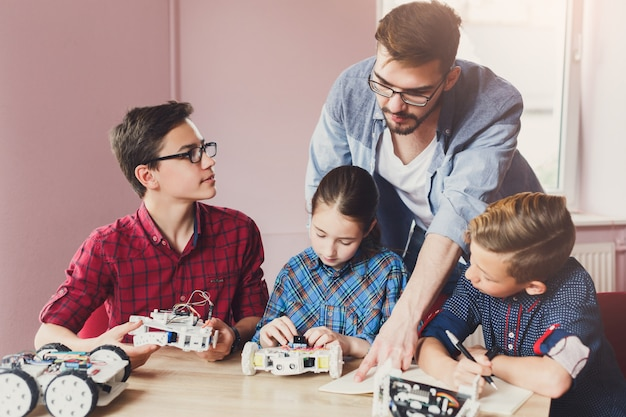 Enfants créant des robots avec un enseignant Photo Premium
