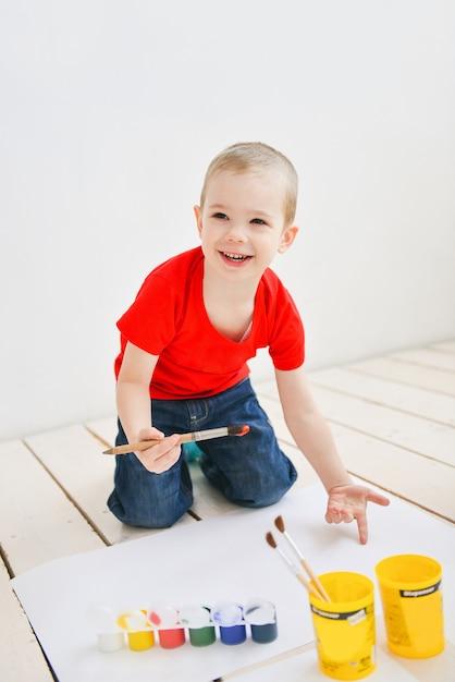 Des enfants créatifs peignent au pinceau sur du papier, des images colorées drôles sur un sol Photo Premium