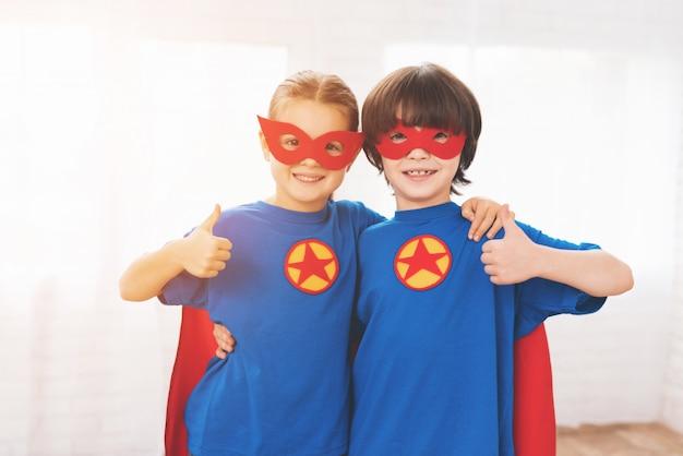 Enfants dans les costumes rouges et bleus des super-héros. Photo Premium
