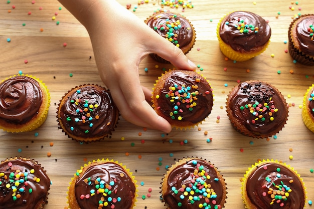 Les enfants dans la cuisine! closeup main d'un enfant choisissant un gâteau au chocolat sur la planche de petit gâteau Photo Premium