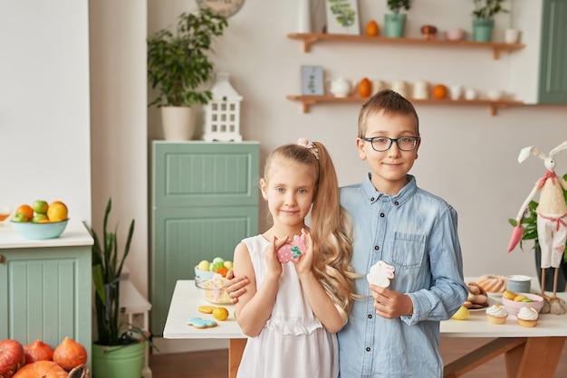 Enfants dans la cuisine le jour de pâques, garçon et fille avec pain d'épices et oeufs de pâques Photo Premium
