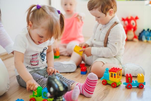Les enfants dans la salle de jeux sur le sol Photo gratuit