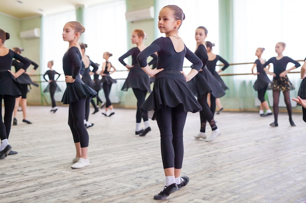 Les enfants dansent avec un entraîneur dans une grande salle de formation. Photo Premium