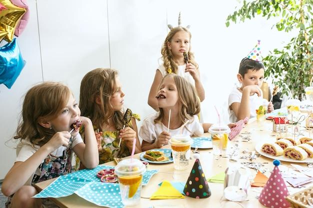 Enfants Et Décorations D'anniversaire. Garçons Et Filles à Table Avec De La Nourriture, Des Gâteaux, Des Boissons Et Des Gadgets De Fête. Photo gratuit