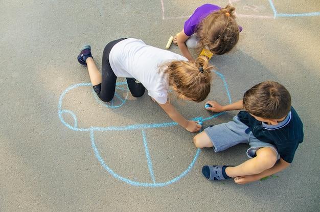 Des enfants dessinent une voiture à la craie sur le trottoir. mise au point sélective. Photo Premium