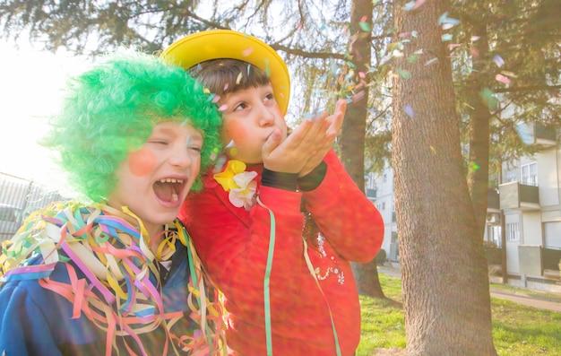 Enfants Drôles Filles Célèbrent Le Carnaval En Souriant Et En S'amusant Avec Des Confettis Colorés Photo Premium