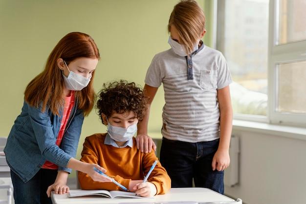 Enfants à L'école Apprenant Avec Des Masques Médicaux Sur Photo gratuit