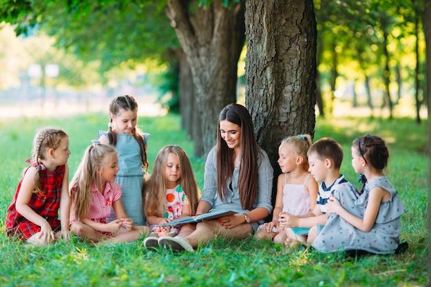Enfants et éducation, jeune femme au travail en tant qu'éducatrice, livre de lecture pour garçons et filles dans le parc. Photo Premium