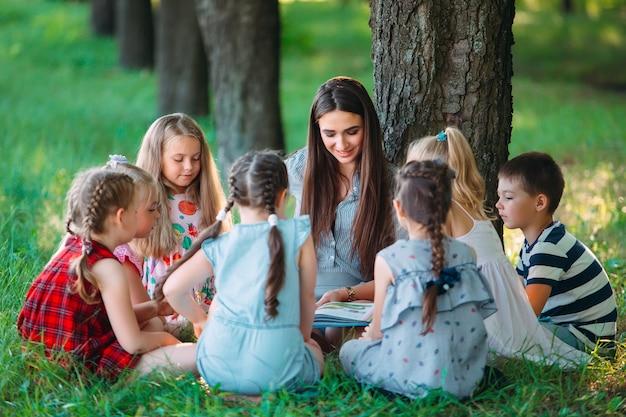 Enfants et éducation, jeune femme au travail en tant qu'éducatrice, livre de lecture pour garçons et filles dans un parc Photo Premium