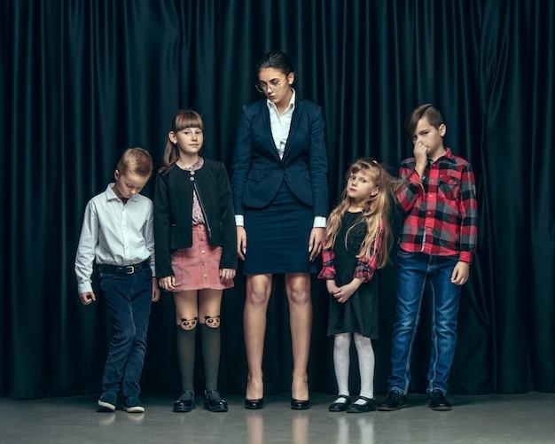 Enfants élégants Mignons Sur Un Espace Sombre. Les Belles Adolescentes Et Garçon Debout Ensemble Photo gratuit