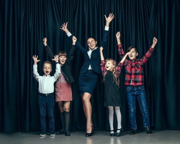 Enfants élégants Mignons Sur Studio Sombre. Les Belles Adolescentes Et Garçon Debout Ensemble Photo gratuit