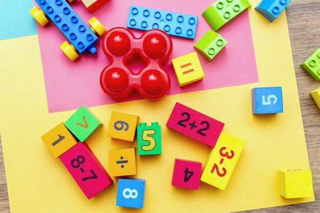 Enfants Enfants Jouets éducatifs Colorés Cubes Avec Des Chiffres Mathématiques Motif De Fond Sur Le Fond Clair. Mise à Plat. Photo Premium