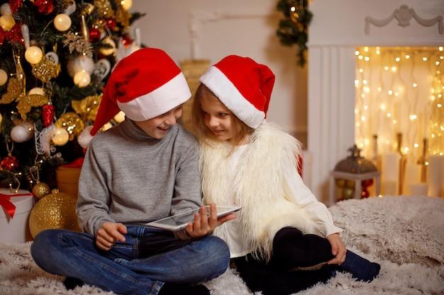 Enfants Excités Près De Sapin De Noël Photo Premium