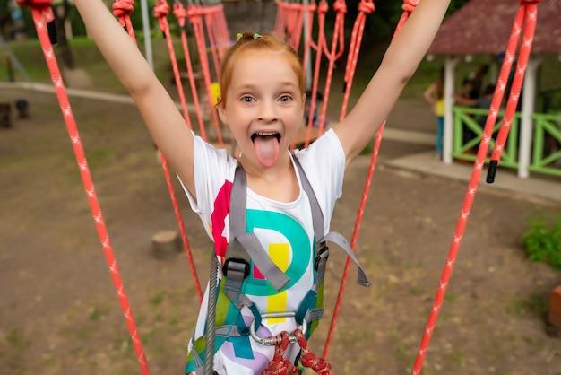 Enfants - une fille court un parcours d'obstacles dans un parc à cordes Photo Premium