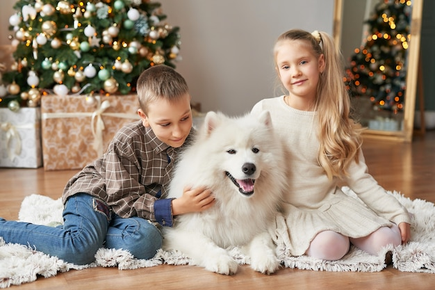 Enfants fille et garçon avec chien samoyède sur scène de noël Photo Premium