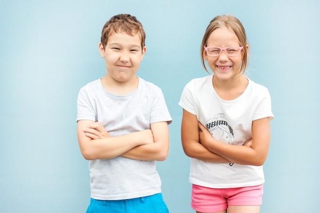 Enfants frère et soeur jumeaux de 8 ans debout avec des grimaces sur fond bleu Photo Premium