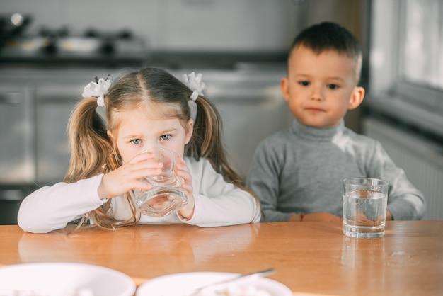 Enfants Garçon Et Fille Dans La Cuisine De L'eau Potable à Partir De Verres Très Doux Photo Premium