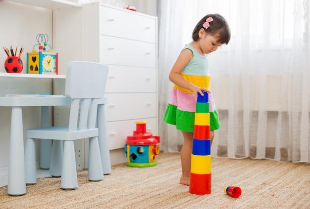 Des enfants heureux d'âge préscolaire jouent avec des blocs de jouets en plastique coloré. Photo Premium