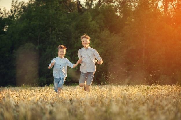 Enfants heureux courir autour du terrain avec dandalions onsummer sunset. Photo Premium