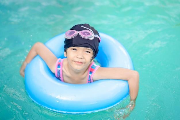 Enfants heureux fille enfant dormir sur la bouée de sauvetage pour nager dans la piscine Photo Premium