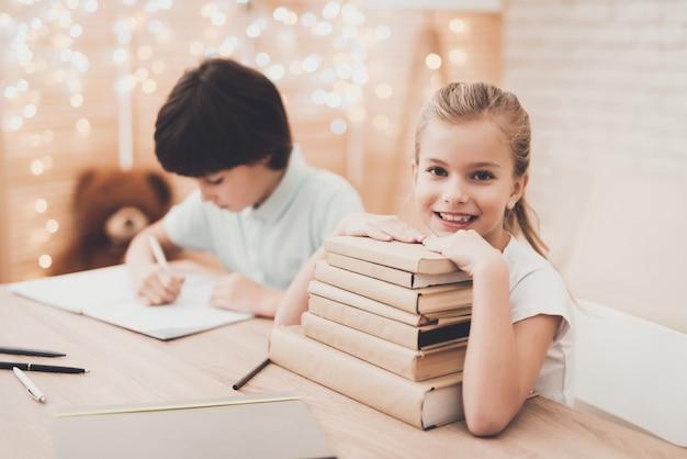Enfants heureux avec des manuels empilés au bureau Photo Premium