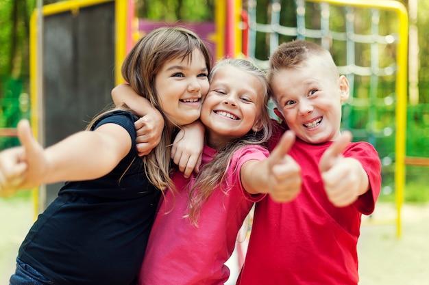 Enfants Heureux Montrant Signe Ok Sur Aire De Jeux Photo gratuit