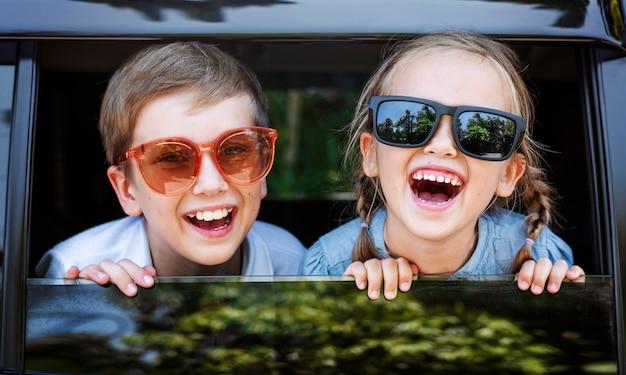Enfants heureux regardant par la fenêtre de la voiture Photo gratuit