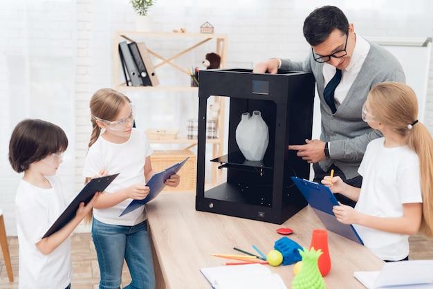 Les enfants impriment différents éléments sur une imprimante 3d avec un enseignant. Photo Premium