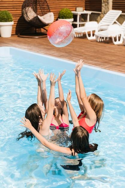 Enfants jouant dans la piscine avec un ballon de plage Photo gratuit